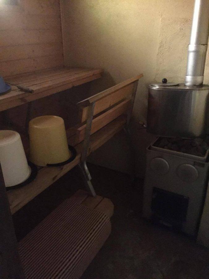 Puulämmitteinen sauna, jossa vesi lämpenee kiukaan padassa.
